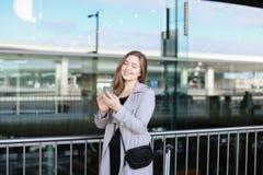 Service de mini-messages européen de femme par le smartphone près de la mallette et de l'aéroport Photographie stock libre de droits