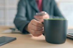 Service de mini-messages de femme d'affaires au téléphone portable pendant la pause-café du bureau photos stock