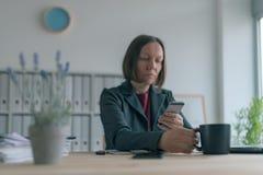 Service de mini-messages de femme d'affaires au téléphone portable pendant la pause-café du bureau photos libres de droits