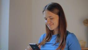 Service de mini-messages de femme enceinte sur un mobile sur la ligne téléphone se reposant sur un sofa dans le salon à la maison banque de vidéos