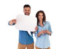 Service de mini-messages de femme tandis que l'homme tient une bulle et des points de la parole Photo stock