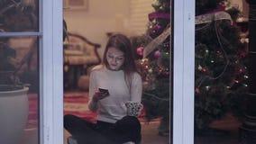 Service de mini-messages de fille dans le smartphone près de la fenêtre avec la tasse banque de vidéos