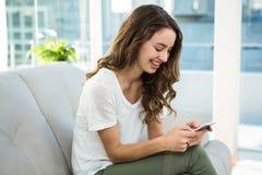 Service de mini-messages heureux de femme sur le sofa photos libres de droits