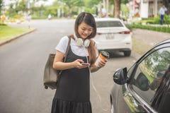 Service de mini-messages heureux de fille avec des amis au téléphone intelligent Photographie stock libre de droits