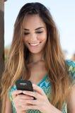 Service de mini-messages heureux de jeune femme photographie stock libre de droits