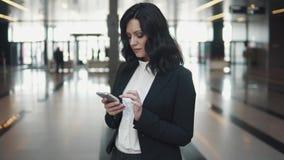 Service de mini-messages de jeune femme à un téléphone portable tout en se tenant dans le lobby d'un immeuble de bureaux moderne banque de vidéos