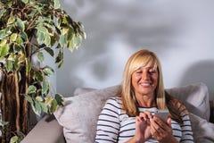 Service de mini-messages mûr de sourire de femme Photos stock