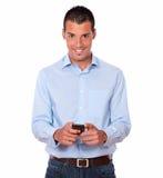 Service de mini-messages magnifique de jeune homme avec son téléphone portable Image stock