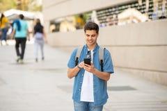 Service de mini-messages masculin de jeune étudiant heureux à son téléphone intelligent dans la ville moderne photos stock