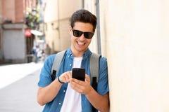 Service de mini-messages masculin de jeune étudiant heureux à son téléphone intelligent dans la ville moderne photos libres de droits