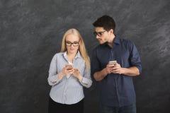 Service de mini-messages de observation de fille d'ami jaloux au téléphone Photo stock