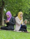 Service de mini-messages occupé de deux étudiants universitaires avec leur smartphone tout en se reposant en parc Photographie stock