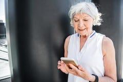 Service de mini-messages plus âgé gai de dame par le téléphone portable extérieur Image libre de droits