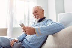 Service de mini-messages plus âgé optimiste d'homme tout en buvant du café Photo stock