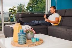 Service de mini-messages de regard sérieux d'homme avec son téléphone et refroidissement sur le divan photos stock