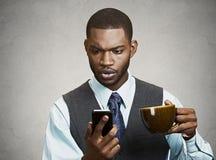 Service de mini-messages sérieux d'homme d'affaires à son téléphone image stock