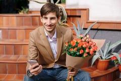 Service de mini-messages de sourire d'homme tout en regardant le téléphone dans des ses mains Photos libres de droits