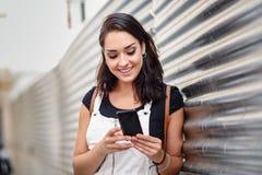 Service de mini-messages de sourire de femme avec son téléphone intelligent dehors Robe de port de denim de fille à l'arrière-pla image libre de droits