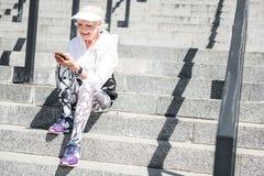 Service de mini-messages supérieur gai de femme par l'intermédiaire de téléphone portable sur des escaliers de ville avec des rai Photos stock
