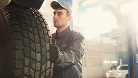 Service de voiture - un mécanicien vérifie la roue de SUV, grande-angulaire photo stock
