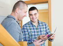 Service employee with tenant at doorway. Smiling communal services employee asking tenant to sign a document Stock Images