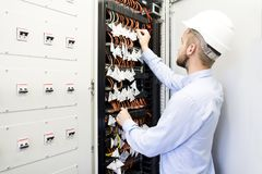 Service engineer in the data center. Worker in a helmet near the switches of optical cables stock photos