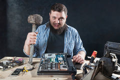 Service engineer with hammer, laptop on the desk Stock Image