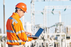 Service engineer working with laptop at heat electric power stat. Engineering supervision. Male service engineer in high visibility reflecting clothing and hard Stock Image