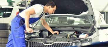 Service et inspection d'une voiture dans un atelier - le mécanicien inspectent photos libres de droits