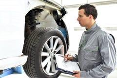 Service et inspection d'une voiture dans un atelier - le mécanicien inspectent photos stock
