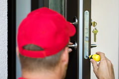 Service för dörrlås - låssmed som arbetar med skruvmejsel royaltyfria bilder