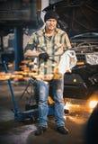 service för utbyte för bunkebilelevator lyftolja Mekanikermananseendet vid bilen och torkar av hjälpmedlet som ser i kameran spar royaltyfri fotografi