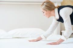 Service hôtelier Made faisant le lit dans la chambre images stock
