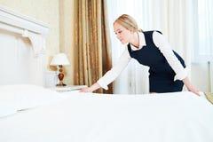 Service hôtelier Made faisant le lit dans la chambre photos stock