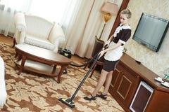 Service hôtelier travailleur féminin de ménage avec l'aspirateur images stock
