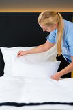 Service in hotel, maid puts clean sheets on bed Stock Photo