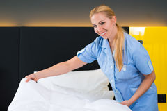 Service in the hotel, put clean sheets on bed Royalty Free Stock Images