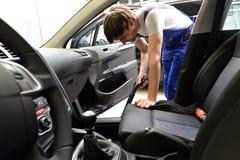 Service i en bilåterförsäljare - mekanikern suger insidan av en bil Arkivbilder
