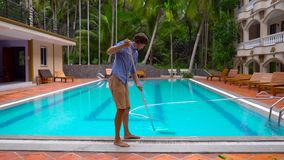Service and maintenance of the pool.Cleaning the pool. Man providing service and maintenance of the pool.Cleaning the pool stock video footage