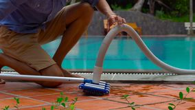 Service and maintenance of the pool.Cleaning the pool. Man providing service and maintenance of the pool.Cleaning the pool stock video