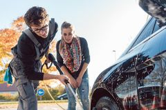 Service man helping woman cleaning her auto in car wash royalty free stock photography