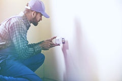 Service man installing power socket in wall. With screwdriver. Copyspace for text stock image