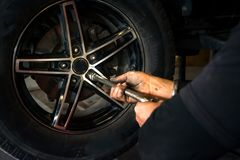 A service man removing the car tyre during car service stock photos