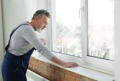 Service man measuring window for installation. Indoors royalty free stock photography