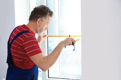 Service man measuring window for installation. Indoors royalty free stock image