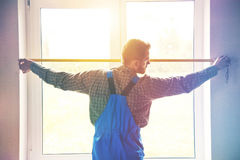 Service man near window with measure tape. Service man installing window with measure tape stock images