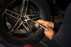 A service man removing the car tyre during car service royalty free stock photos