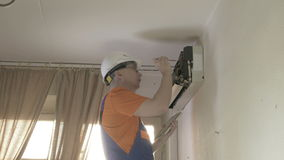 Service man to clean air conditioner stock video