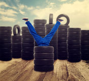 Service mechanic legs stick out of the tire pile. Repairman, wheel mounting. Tyre shop stock images