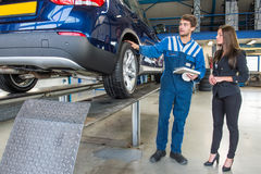 Service mechanic showing his work on a customers car to the client. Dedicated and professional service mechanic, showing a customer around her car, which has royalty free stock photo